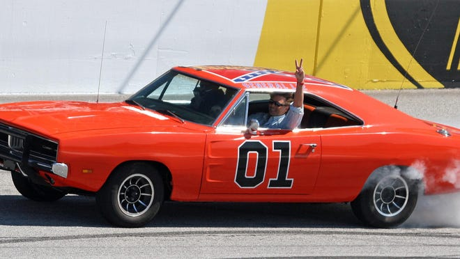 """Actor John Schnieder, star of the 1980's U.S. television show """"The Dukes of Hazzard,"""" waves from the General Lee before the Kobalt Tools 500 auto race in 2008 at Atlanta Motor Speedway in Hampton, Georgia."""