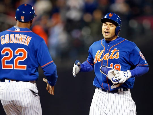 New York Mets catcher Travis d'Arnaud (18) celebrates a 2-RBI double against the Atlanta Braves with Mets first base coach Tom Goodwin (22) during the fifth inning at Citi Field.