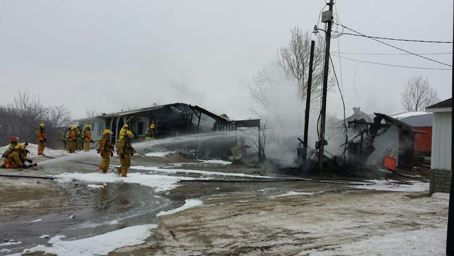 Firefighters battle a blaze at the Eugene and Bevery Lammers residence on Liner Road near Brandon Wednesday afternoon.