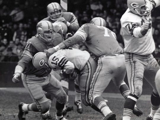 Nov 22, 1962; Detroit, MI, USA; FILE PHOTO; Green Bay Packers quarterback Bart Starr (15) is tackled by Detroit Lions defensive tackle Alex Karras (71) and Darris McCord (78) at Tiger Stadium.