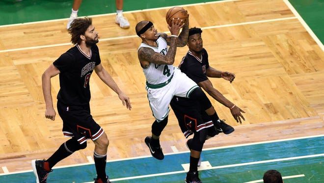 Boston Celtics guard Isaiah Thomas (4) drives to the basket past Chicago Bulls center Robin Lopez (8) and forward Jimmy Butler (21) during the second half in game five of the first round of the 2017 NBA Playoffs at TD Garden.
