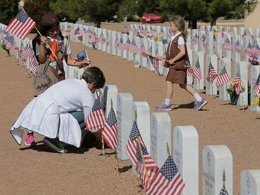 Lailah Johnson 8, Victoria Alvardo and Karly Spencer 7, put out American flags on the headstones of former military members and their family members that are buried at Fort Bliss National Cemetery.