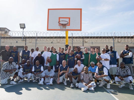 Golden State Warriors members and inmates pose for