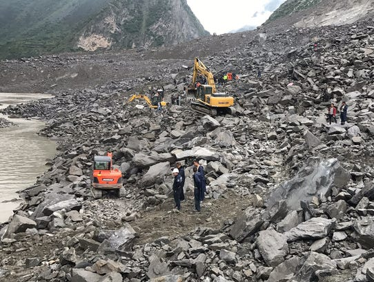 Rescuers work at the site of a massive landslide where