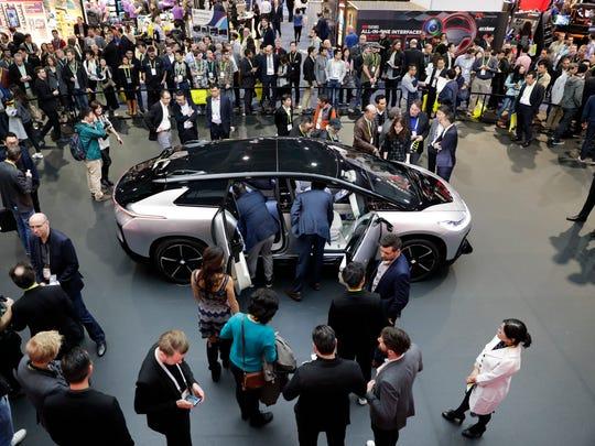 People gather around the Faraday Future's FF91 electric
