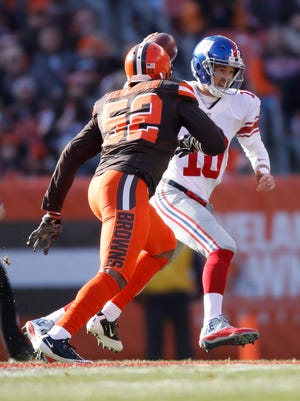 Eli Manning of the New York Giants tries to avoid a tackle by Corey Lemonier of the Cleveland Browns during the first quarter at FirstEnergy Stadium on November 27, 2016 in Cleveland, Ohio.