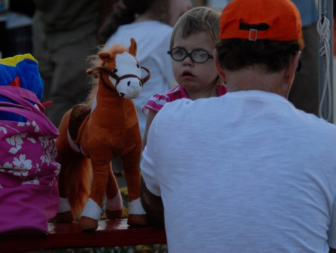 Ariah Owen of Pocomoke City, Md., sits by her stuffed pony as she takes in the sights of the 89th Volunteer Fireman's Carnival Saturday June 28, 2014 on Chincoteague. The annual carnival opened this weekend.