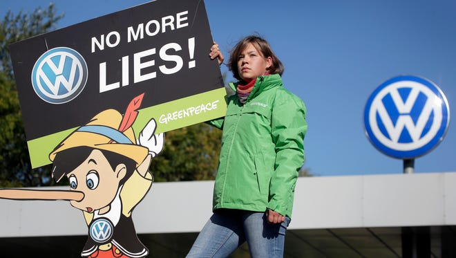 An activist of the environmental protection organization 'Greenpeace' holds a protest poster in front of a factory gate of the German car manufacturer Volkswagen in Wolfsburg, Germany, Friday, Sept. 25, 2015.
