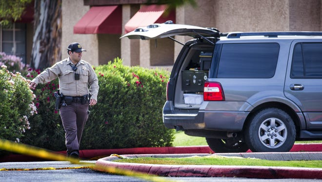 A Maricopa County Sheriff's deputy stands near a taped-off crime scene at the University Ranch apartments near Price and University in Tempe, early Wednesday morning, May 11, 2016.
