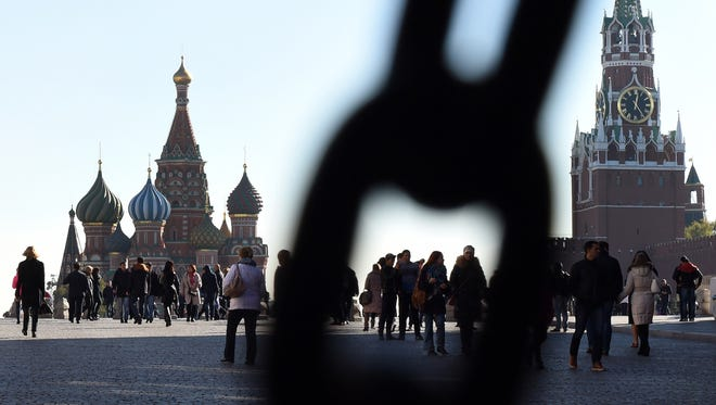 People walk across Red Square, with the Kremlin's Spasskaya Tower (right) and St. Basil's Cathedral (left), in central Moscow in a 2015 file photo.
