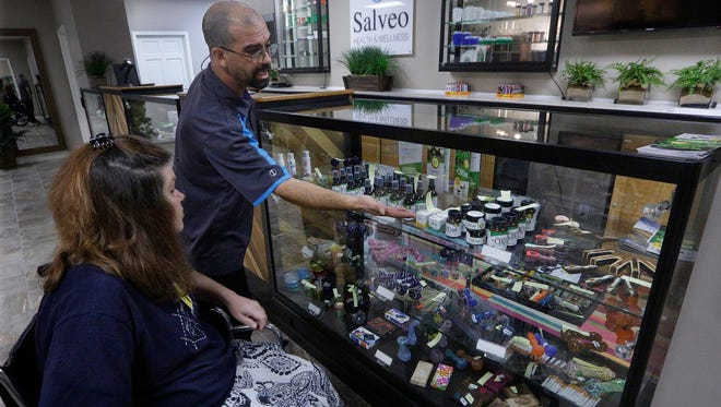 FILE – In this Oct. 20, 2015, photo, Shamay Flaharty of Lewiston, Ill., who has multiple sclerosis and is hoping cannabis will help ease her pain and headaches, meets with Eric Sweatt, partner and manager of Salveo Health and Wellness, a licensed medical cannabis dispensary in Canton, Ill. Ohio's medical marijuana law takes effect Sept. 8, 2016, and Republican Ohio state Sen. Bill Seitz says changes may be required to part of the law that sets aside a piece of the state's future pot business for minorities, provisions that The Associated Press reported may be unconstitutional.