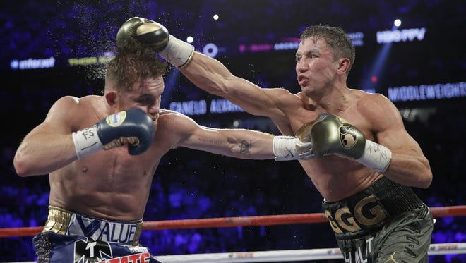 Gennady Golovkin, right, connects with a right to Canelo Alvarez during a middleweight title fight Sunday, Sept. 17, 2017, in Las Vegas. (AP Photo/John Locher)