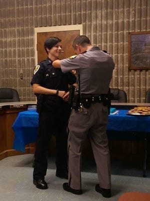 The Uniontown Police Dept and city of Uniontown hosted an open house reception for Officer Jewely Settle. Approximately 35 persons attended and here her Husband Shane Settle pins her new badge onto her uniform. Officer Settles Family attended as well.