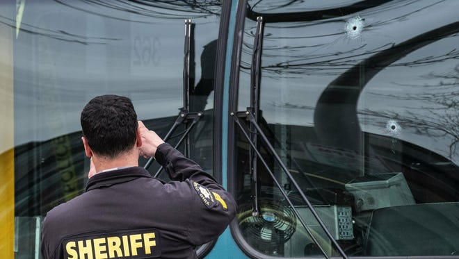 Investigators examine bullet holes in the driver's side window of a Metro Bus on Northeast 125th Street, between 32nd and 33rd Avenues Northeast after a shooting in Seattle, Wednesday March 27, 2019.