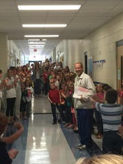 Second-grade students at Nelson-Wilks-Herron Elementary welcome back Coach Marcus McCain on Monday morning.