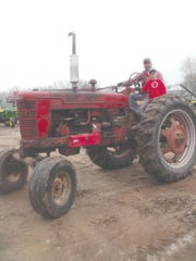 Brock and Brody Smith drive their Farmall, making the