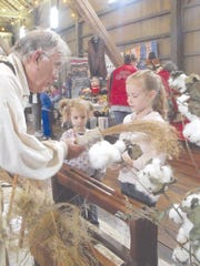 Sophia and Anneliese Wolfenberger learn how to process flax into linen at John Lindsey's demonstration booth. The girls, their sister, and mother came from Fort Wayne to enjoy the Fiber Art Celebration.