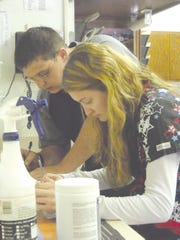 Cheyenne McCullough works with Vet Technician Dereck Fowler on preparing medications for clients at the Shiery Animal Clinic. McCullough earned class credits through her work experience.