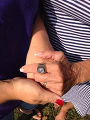 Melanie Elliot and her mother, Rita Slessman, cherish the class ring that belonged to Elliot's brother and Slessman's son, Victor Michael Perkins, Jr.