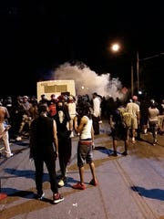 Police fire tear gas into the crowd of protesters on Old Concord Road late Tuesday night, Sept. 20, 2016, in Charlotte, N.C. A black police officer shot an armed black man at an apartment complex Tuesday, authorities said, prompting angry street protests late into the night. The Charlotte-Mecklenburg Police Department tweeted that demonstrators were destroying marked police vehicles and that approximately 12 officers had been injured, including one who was hit in the face with a rock.