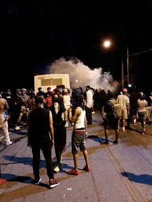 Police fire tear gas into the crowd of protesters on Old Concord Road late Tuesday night in Charlotte, N.C.