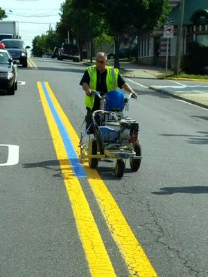 """A DPW worker paints a """"thin blue line"""" on Paterson Avenue in East Rutherford."""