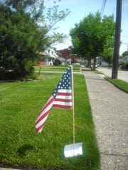 Pictured is a row of U.S. flags that have been placed in front of residential homes in Totowa, compliments of Century 21 Gold Properties Realty, Inc. on Totowa Road.