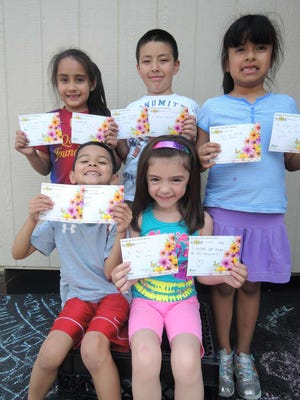 Students at School 3 hold up index cards with their random act of kindness.