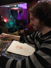 Freelance cartoonist Dezi Sienty creates caricatures for guests at Paula's Public House.
