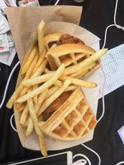 A chicken and waffle sandwich with fries.