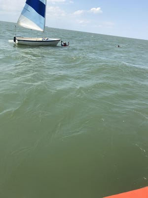 The Coast Guard rescues two people from the water off Cape Charles, Virginia on Saturday after their boat capsized.