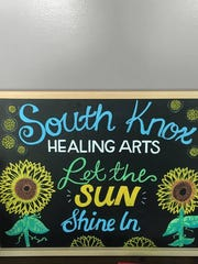 A chalkboard sign stands outside of South Knox Healing