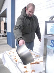 Corey Moyer pours maple syrup 'taffy' onto snow to cool it for visitors to appreciate during the Michigan Maple Syrup Weekend.