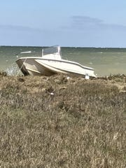A 17-foot recreational fishing vessel sits aground on Adam Island in the Chesapeake Bay on April 29.