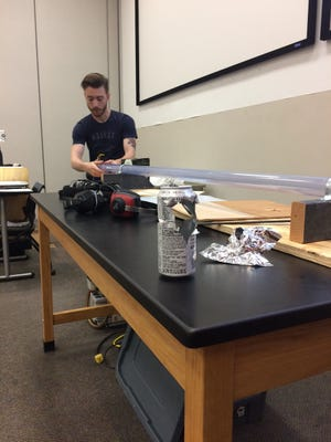 APSU Department of Physics, Engineering and Astronomy graduate Jonathan Bunton prepares the ping pong cannon for the second shot.