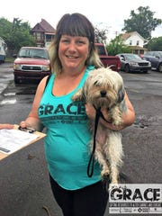 Volunteer Angel Mikula with dog Paris assisting with morning check in and paper work