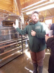 Owner Daniel Olson explains the various machines to the attendees  of the sugarbush's annual Maple Festival.