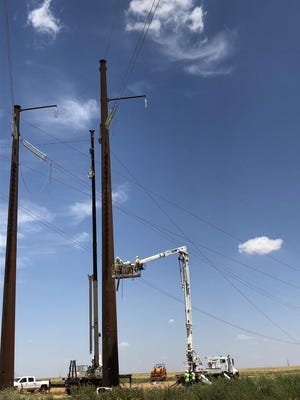 Workers with Xcel Energy connect a supply structure as part of the 240-mile Power for the Plains grid enhancement project, which was recently completed between West Texas and southeastern New Mexico.