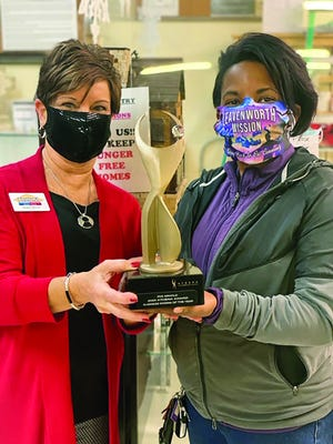Rosalee Robinson, president of the Women's Division of the Leavenworth-Lansing Area Chamber of Commerce, presents the 2020 Athena Award to Iris Arnold, founder of the Leavenworth Mission Community Store and Food Pantry.