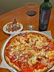 A large Michael's Favorite pizza, with a slice of turtle cheesecake, and Romance red wine, served at Michael's Pizza, at 2629 Beaver Ave., Suite 13, in  Des Moines, on Friday, April 8, 2011.