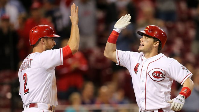 Cincinnati Reds second baseman Scooter Gennett (4) is congratulated by Cincinnati Reds shortstop Zack Cozart (2) after hitting a three-run home run in the seventh inning during the game between the Milwaukee Brewers and Cincinnati Reds on Tuesday, Sept. 5 at Great American Ball Park.