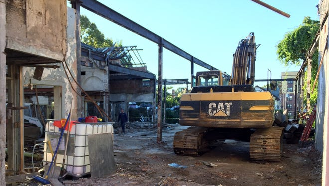 Workers demolish a former train station at 222 E. Third St. in Mount Vernon on Tuesday.