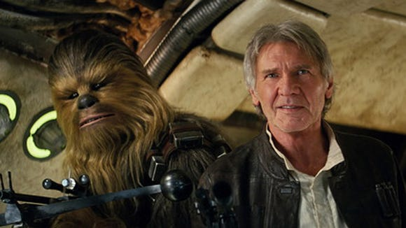 """This photo provided by Lucasfilm shows Peter Mayhew as Chewbacca and Harrison Ford as Han Solo in """"Star Wars: The Force Awakens,"""" directed by J.J. Abrams."""