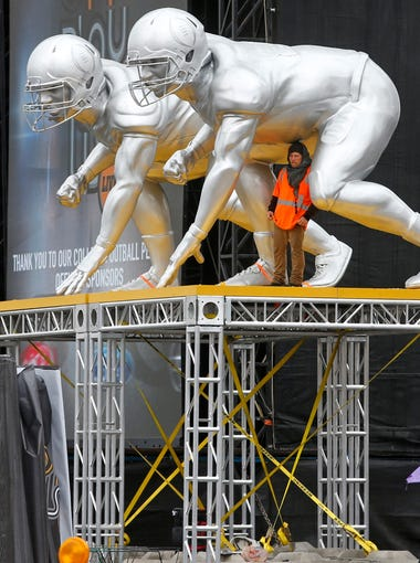 Crews work through rain to set up for the College Football Playoff Championship fan events  in downtown Phoenix on Thursday, January 7, 2016.