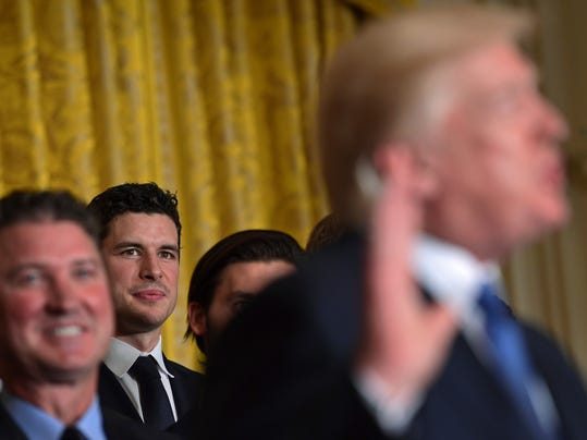 Pittsburgh Penguins captain Sidney Crosby, third from left, listens as President Donald Trump, right, speaks about the 2017 NHL Stanley Cup Champion Pittsburg Penguins, Tuesday, Oct. 10, 2017, during a ceremony in the East Room of the White House in Washington. (AP Photo/Susan Walsh)