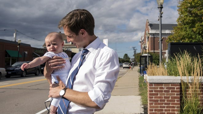 Jake Auchincloss, declared winner of the 4th Congressional District seat, holds his five-month-old son, Teddy, while waving to supporters in Needham, Sept. 1, 2020.