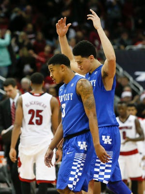 Kentucky's Devin Booker raises his arms in victory as he and fellow freshman Tyler Ulis walk off the court after defeating Louisville 58-50 in a Dec. 27 game at the KFC Yum! Center.