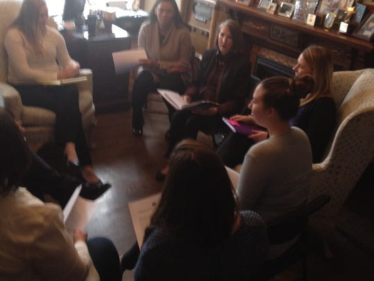 Barbara Schlichting (holding open binder), Executive Director of Somerset Treatment Services in Somerville, meets with several of the organization's counselors and staff members to review treatment plans