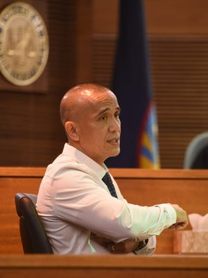 Mark Torre Sr., a police lieutenant, points to the area where he says Elbert Piolo was wounded during his son, Mark Torre Jr.'s murder trial at the Superior Court of Guam on Feb. 8, 2017. The senior Torre said he saw a hole under Piolo's right arm, but the wound was clean.