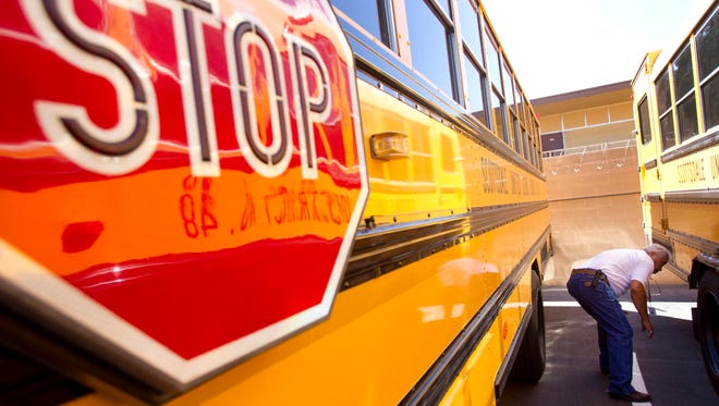 Miguel Porras, bus driver for Scottsdale Unified School District in Arizona inspects his bus after his morning route.
